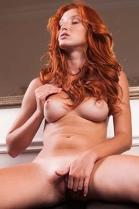 Perky redhead Foxy T reveals her delicious pink pussy