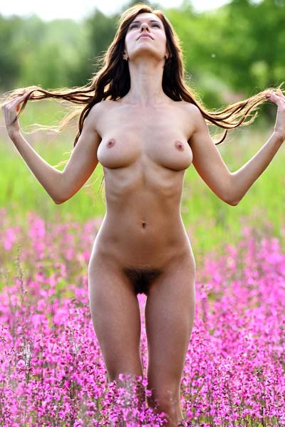 Alluring busty brunette Susi R undresses and showcases her curves in a flower field