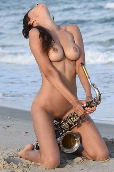 Naked busty babe Susi R plays the saxophone on the beach