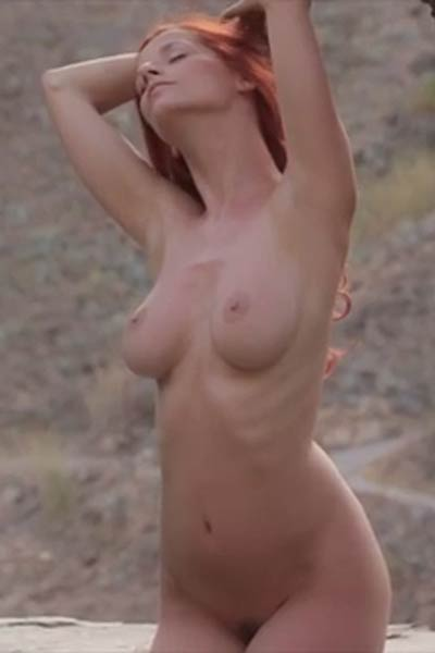Tempting redhead hottie Ariel displays her fantastic assets in a stone garden