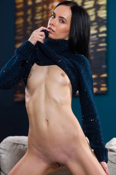 Adorable black haired doll Sasha W takes off her clothes and poses naked on the sofa