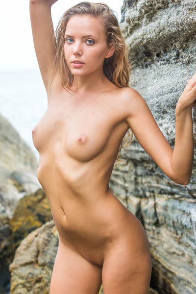 Spectacular blonde babe bares her genuine body as she poses in the water by the rocks