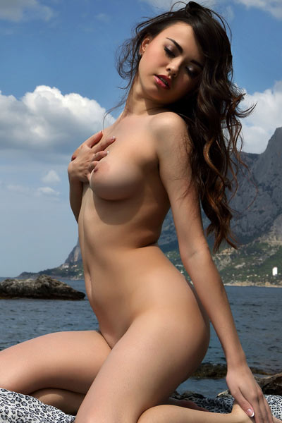 Adorable young chick teases with her petite smooth body on the beach
