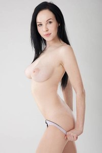 Hot and horny black haired cutie with huge tits strips off for you