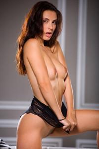 Stunning brunette vixen sensually teases her petite body on the sofa