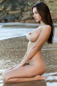 Fabulous brunette doll shows off her perfect body on the beach with a teasing smile on her face