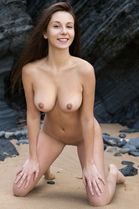 Top class brunette is already naked posing on the beach showing off her perfect boobs