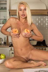 Top class blonde model gives us a perfect view on her busty body as she poses in the kitchen
